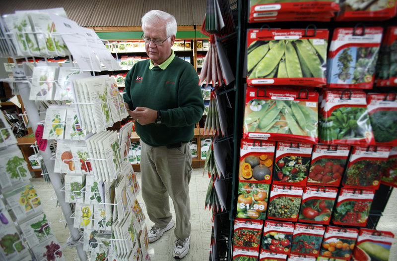 Manager Jerry Holub looks over seed packages at the Earl May Nursery and Garden Center in Des Moines, Iowa. The government's color-coded map of planting zones often appears on the back of the packets. Holub doesn't think the shifting of Des Moines to a warmer zone will have much of an impact there, but it may mean gardeners can try passion flowers.