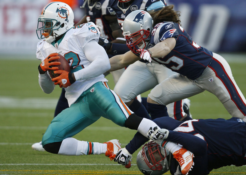 Ross Ventrone, at right, had his first career tackle for the New England Patriots during a Dec. 24 game against the Miami Dolphins, emerging from his defensive back position to bring down Reggie Bush.