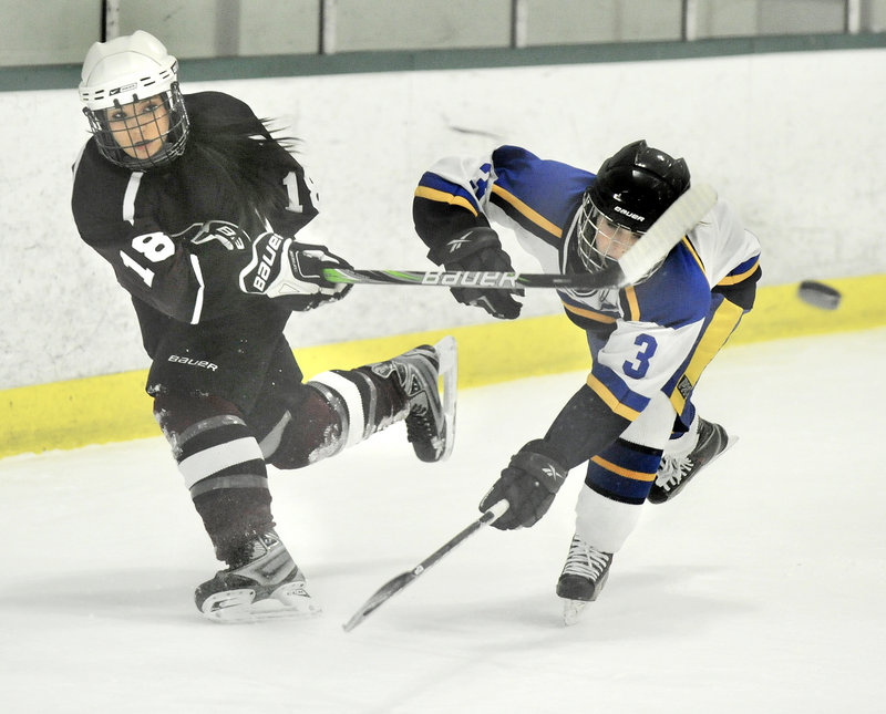 Chelsey Andrews of Greely clears the puck from her zone while pressured by Falmouth's Abby Payson.