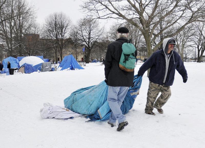Steve Demetriou, left, and Deese Hamilton drag a tent through Lincoln Park to a Dumpster Thursday.