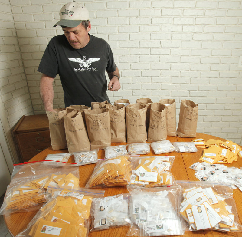 Berard sorts pumpkin seeds that will be mailed to club members. Growers germinate their seeds indoors, moving the plants to progressively larger containers until the weather warms up enough to plant them outside.