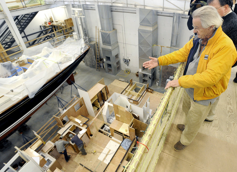 At Lyman-Morse Boatbuilding of Thomaston, Stanley Paris gets a bird's-eye view Wednesday as workers construct the interior of his Paris 63 sailboat below.