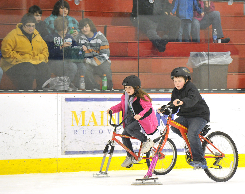 Briana Baillargeon, 8, races neck and neck with her brother, Jordan, 10. A Community Bicycle Center volunteer adapted bikes for the ice by adding some of his old skates.
