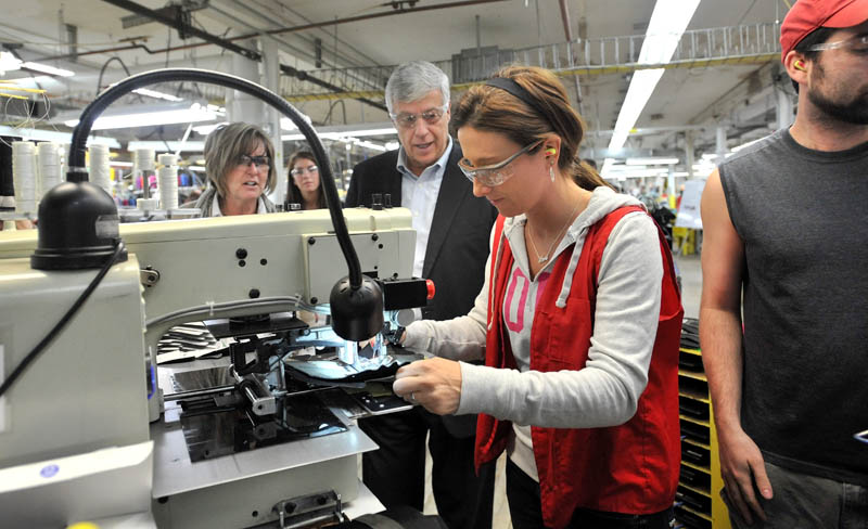 Rep. Mike Michaud, center, speaks with New Balance factory employee Tiffany Whitney while touring the New Balance shoe factory in Norridgewock this morning. Rep. Michaud toured the plant and picked up a pair of size 12D running shoes for President Obama.