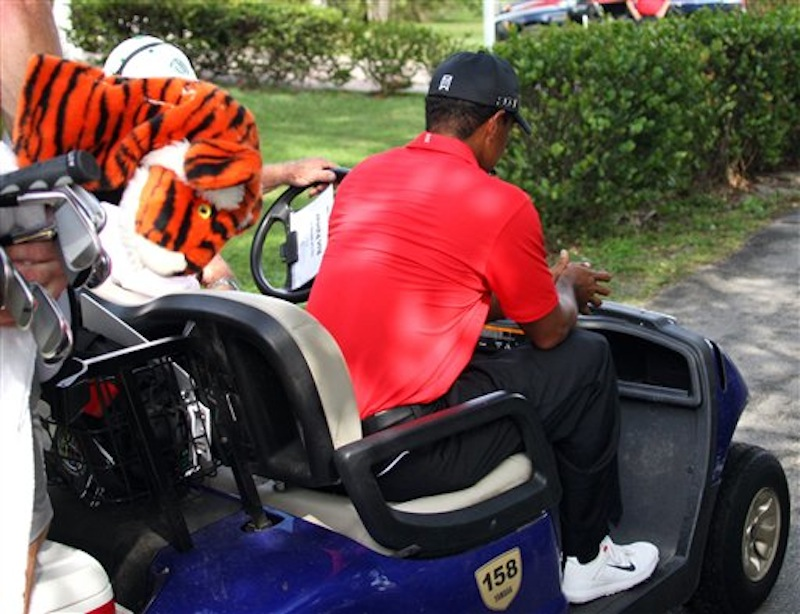 Tiger Woods is driven away in a cart after hitting off the 12th tee during the final round of the Cadillac Championship golf tournament on Sunday, March 11, 2012, in Doral, Fla. Woods withdrew from the tournament. (AP Photo/Wilfredo Lee)