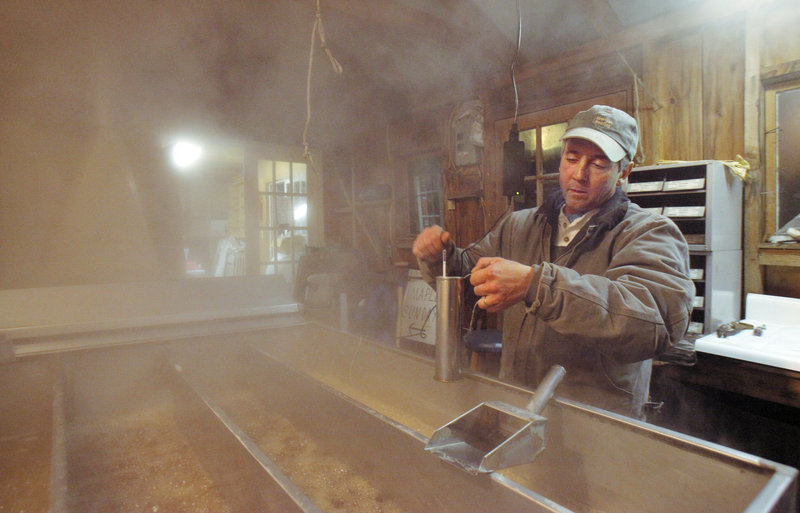 Mark Cooper checks the density of his maple syrup with a hydrometer while boiling sap at his sugar house in Windham earlier this month.