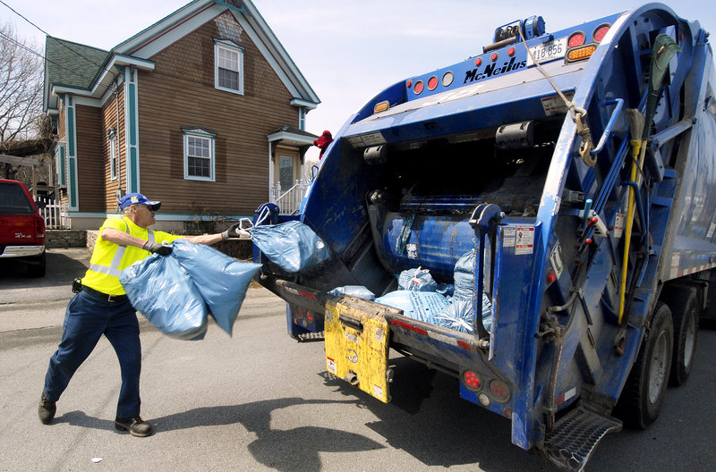 A worker tosses blue Portland trash bags into a garbage truck on Dalton Street.