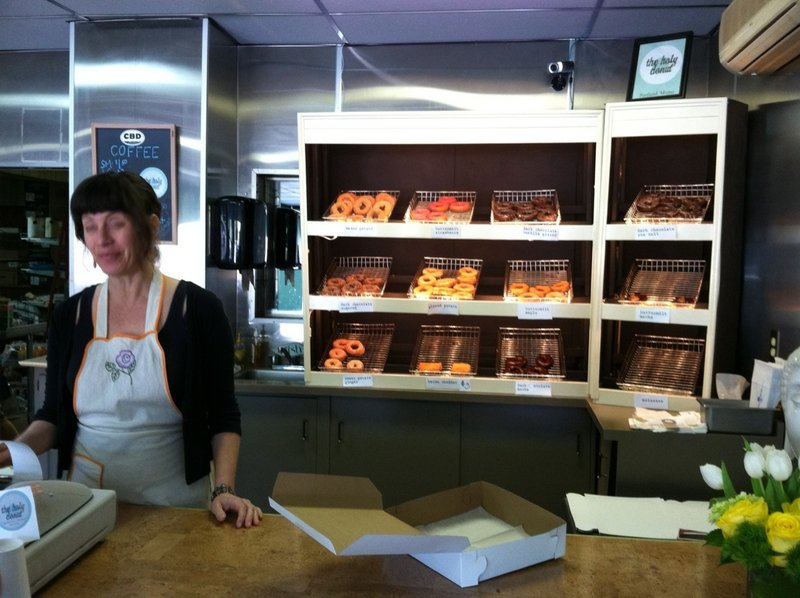 Leslie Deane works the counter at the new Holy Donut, which opened last week in the former Terroni's Market near Hadlock Field on Park Avenue in Portland. Below, an assorted dozen.