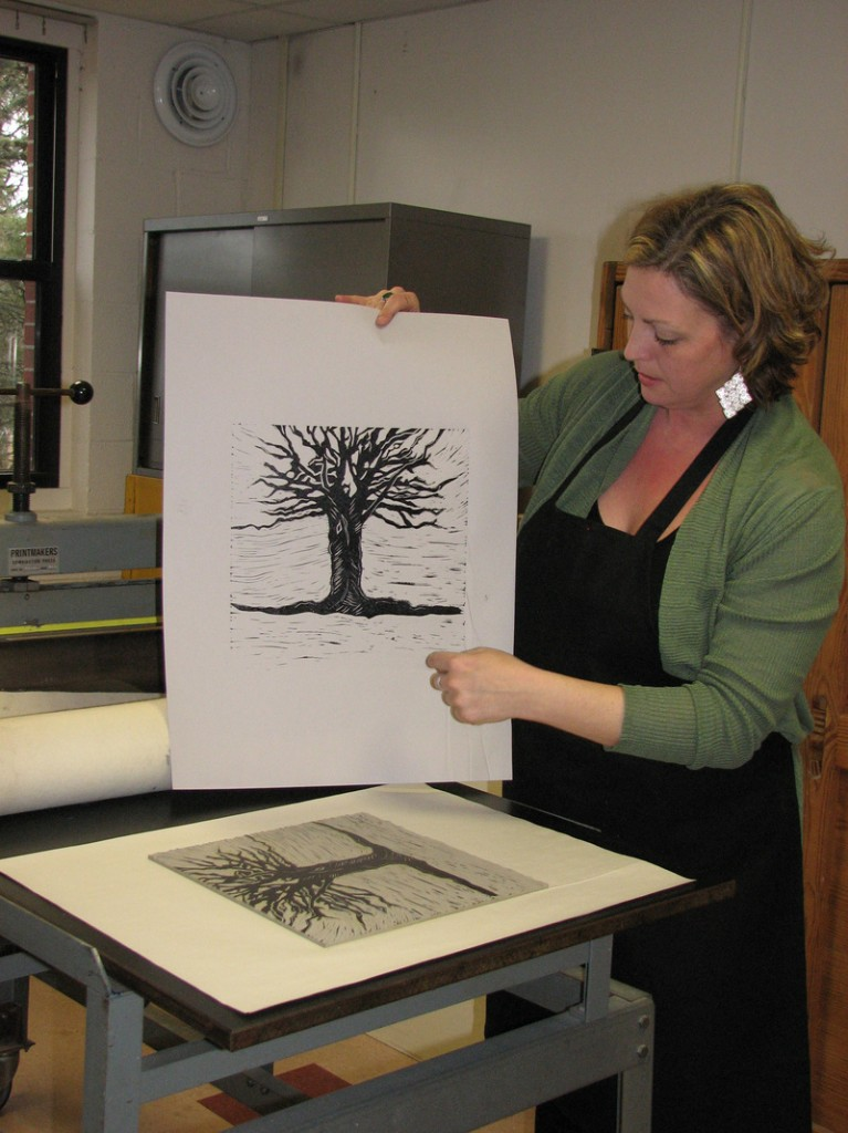 """Hosanna Jensen, a UMaine-Machias student and member of the design team, studies an image being considered for the cover of """"Julia and the Illuminated Baron."""""""