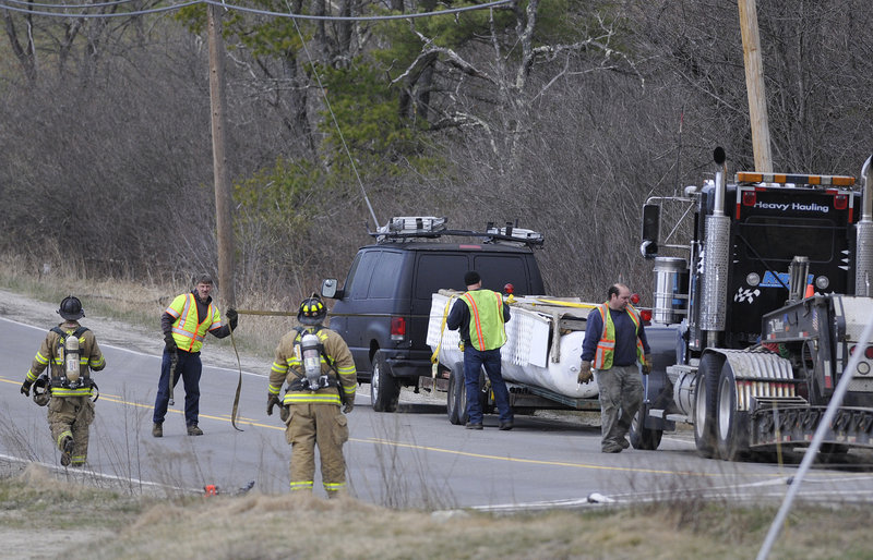 Above, emergency responders assist Monday before a black van transporting propane tanks is loaded onto a flatbed truck on River Road in Windham. Below, the van and truck are headed for a gravel pit in Gorham, where any remaining propane was to be burned off.