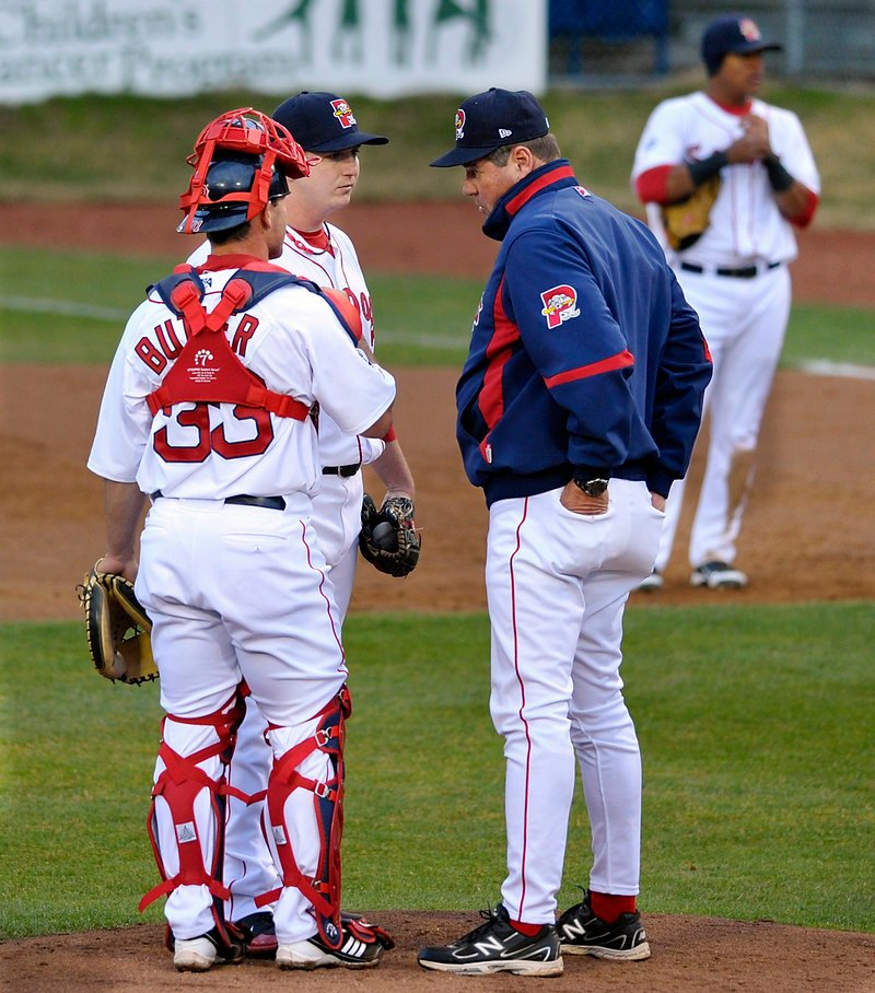 Ralph Treuel, the Sea Dogs' pitching instructor, visits with pitcher Brock Huntzinger and catcher Dan Butler as Huntzinger struggled early in the game.