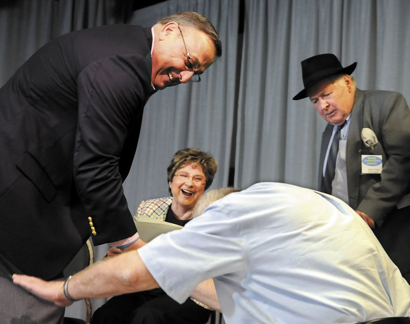 Pat Thatcher's comical greeting of Gov. Paul LePage, left, elicits laughter from LePage, tax activist Mary Adams and John Frary at a Tax Day Rally in Lewiston on Sunday.