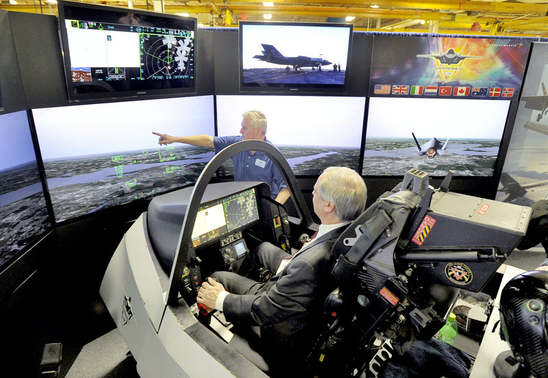 Maine's senior economic adviser John Butera gets flight instruction Friday from Tony Stutts at Lockheed Martin's demonstration of an F-35 fighter jet in a simulator at Pratt & Whitney in North Berwick. Lockheed Martin is building the jets that will use engines manufactured at the Maine plant.