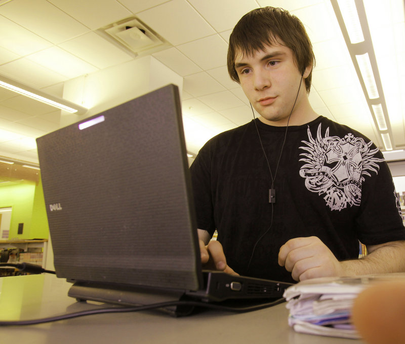 Sean Bouchard, a senior at Portland High School, uses his school-issued netbook computer at the Portland Public Library. New restrictions will block access to social media and video streaming sites for users of the school equipment.