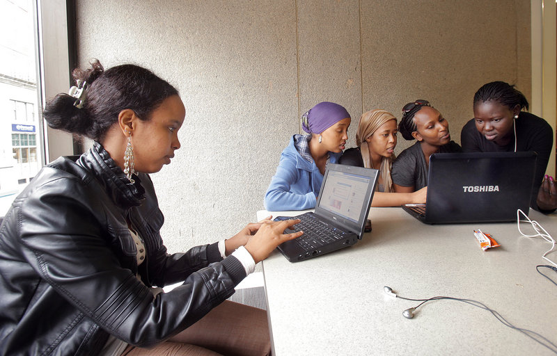 Fathia Elmi, left, a senior at Portland High School, uses a school-issued netbook computer while her friends, from left, Simane Ibrahim, Fatush Jama, Chantal Namuhoza and Linda Nag look at a website on Namuhoza's personal laptop at the Portland Public Library on Thursday.