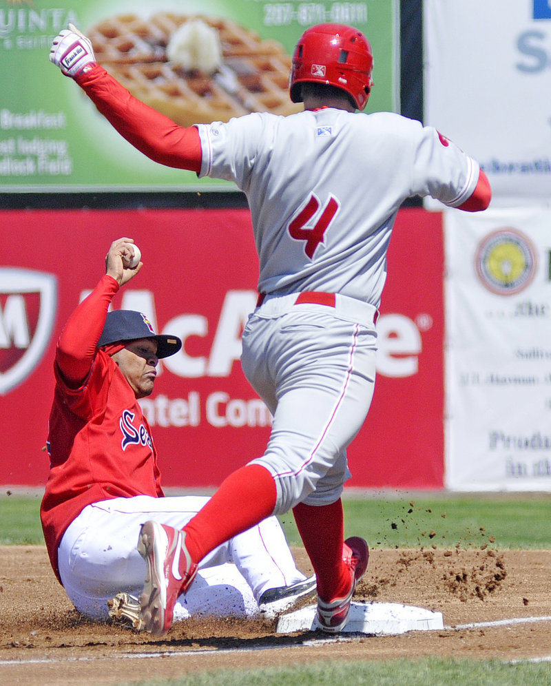 Reynaldo Rodriguez of the Sea Dogs gets to first ahead of Reading runner Darin Ruf in Sunday's game at Hadlock Field. The Phillies won 4-2.