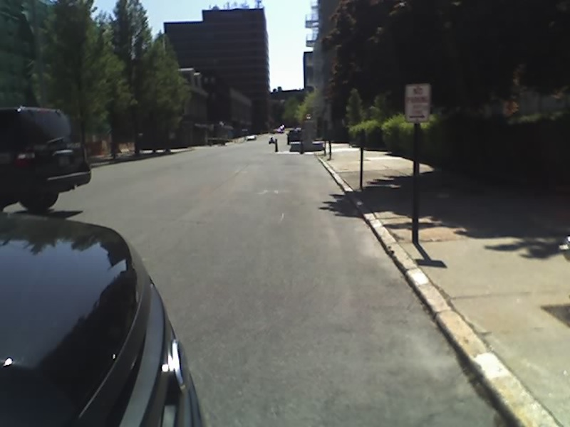 In the distance, a metallic robot controlled by the Portland Police Department rolls down Federal Street toward a water fountain and United State Postal Service mailbox on the right side of the road. Police were alerted around 1 p.m. to a suspicious package in the mailbox, which sits behind the Portland Fire Department.