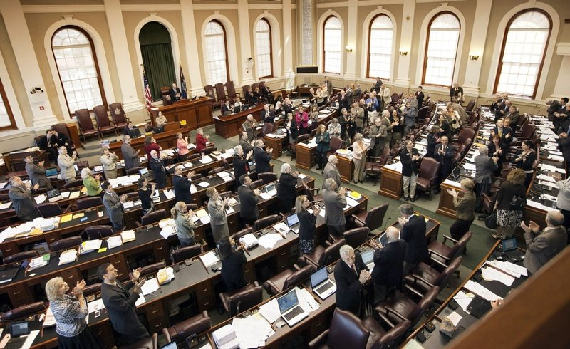 Legislators stand and applaud visitors in the House chamber during a session last month at the State House. Today, legislators are expected to debate a budget tailored by the Republicans to get the governor's support.