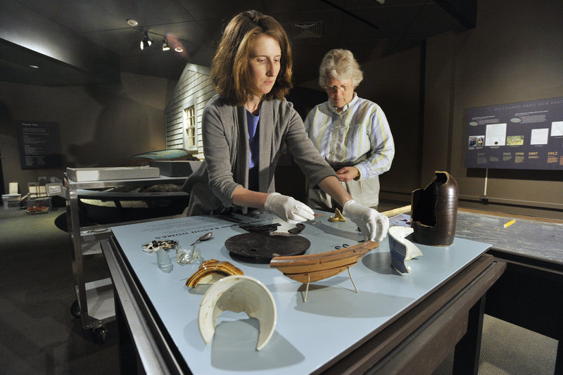 """Kate McBrien and Linda Carrell arrange artifacts from Malaga Island for the exhibit """"Malaga Island, Fragmented Lives"""" at the Maine State Museum in Augusta."""