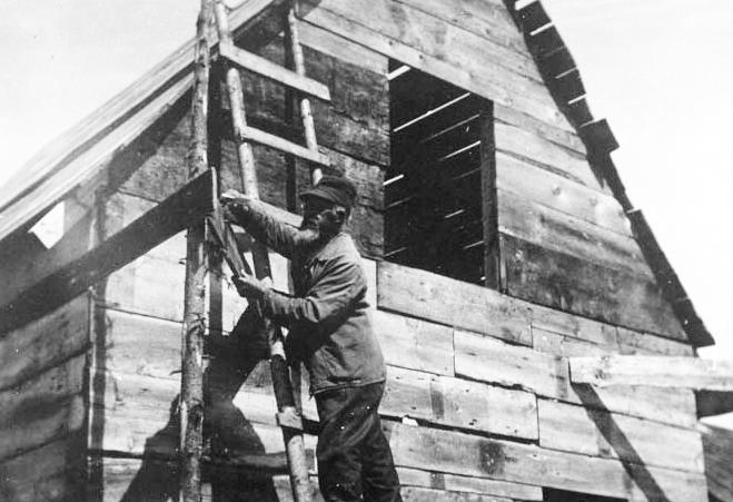 John Eason repairs a building on Malaga Island in 1908.