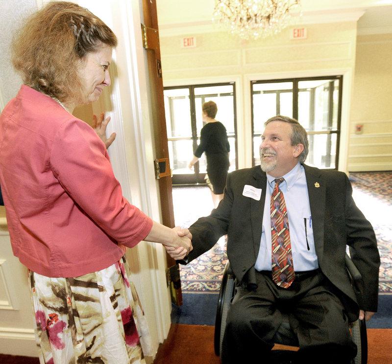William Schneider greets Karen Harrison of Portland before a forum Thursday at Sable Oaks Marriott in South Portland.
