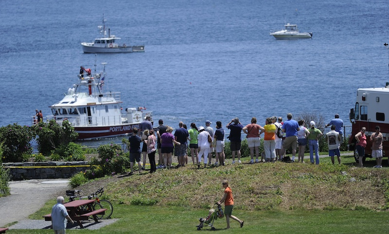 A crowd gathers at Fort Williams Park in Cape Elizabeth, where a plane went down just offshore in Casco Bay on Sunday.