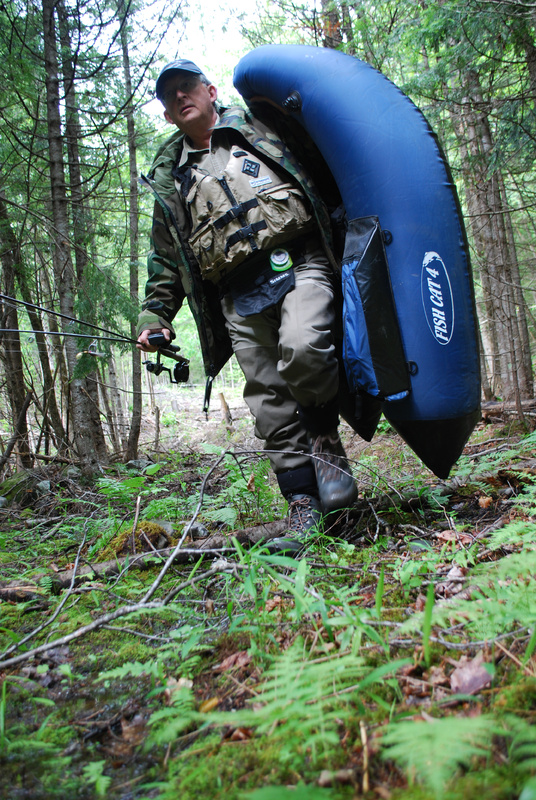 Jerry Derosier hikes in a quarter-mile from the road to Mud Pond in Embden to survey it for the state. Derosier is one of the volunteers who are helping the state on its brook trout pond survey.