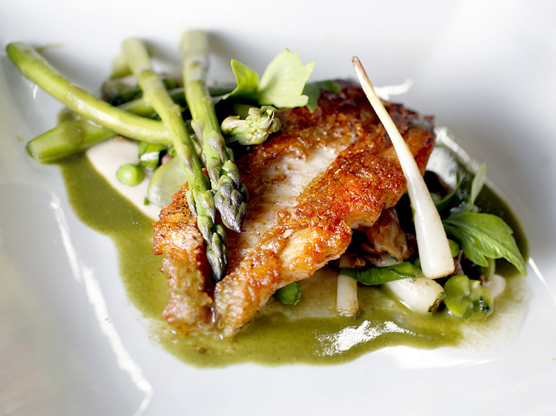 Pan-roasted red fish with spring vegetable fricassee and asparagus veloute, at Grace in Portland.