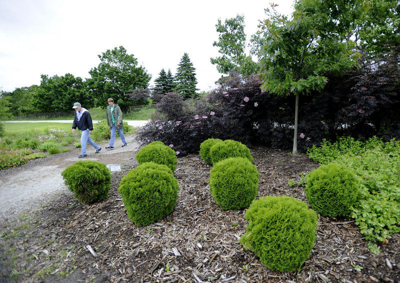 Wayne Wilson, left, of Old Orchard Beach and Eric Cushing of Scarborough walk through the YardScaping Gardens at Back Cove on Tuesday.