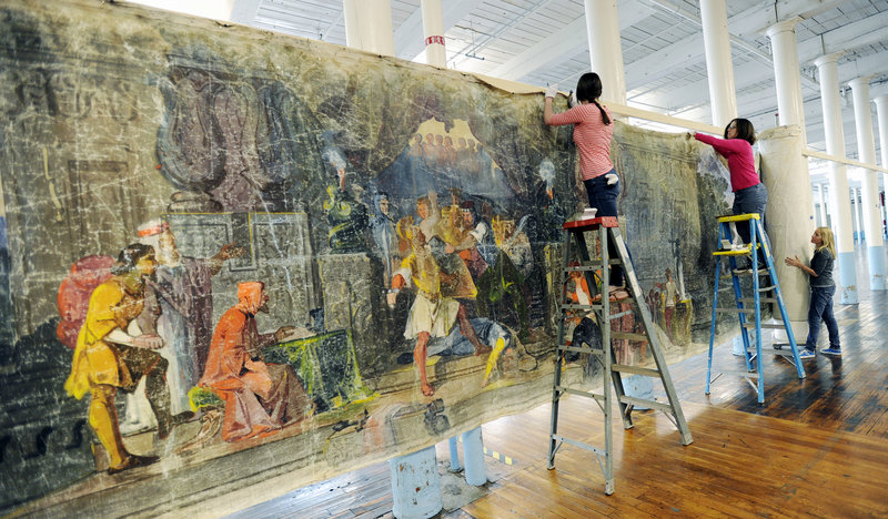 """Anna Kelley, left, Saco Museum director Jessica Skwire Routhier and Marie O'Brien hang the scroll, which was created in 1851 and based on the 1678 book by John Bunyan, """"The Pilgrim's Progress."""""""