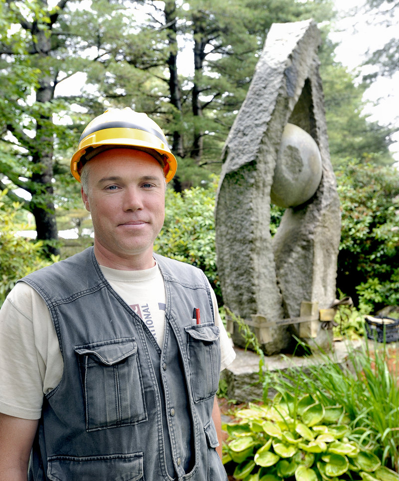 """Sculptor Jesse Salisbury stands in front of """"Tidal Moon,"""" his 14-foot granite artwork, as it was being readied for transport last Saturday from the Yarmouth residence of William and Mary Louise Hamill."""