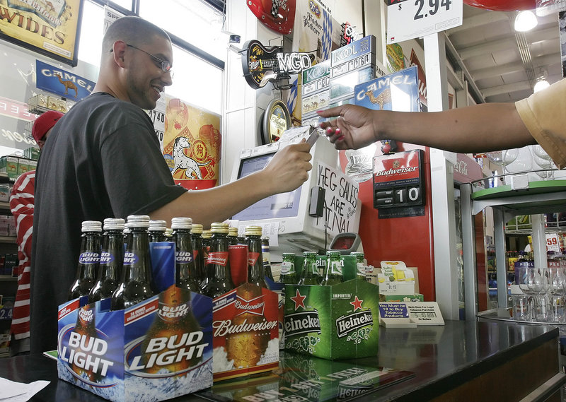 A clerk checks the ID of a customer buying beer at a store in Nashville, Tenn., in 2006. Parents need to be role models of lawful behavior by refusing to host gatherings where underage drinking is going on, a reader says.