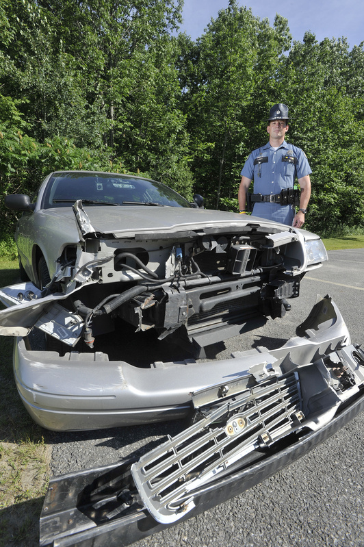 Maine State Police Trooper Douglas Cropper is shown Saturday beside his police cruiser, which was damaged while stopping a wrong-way driver on I-295 on Friday.
