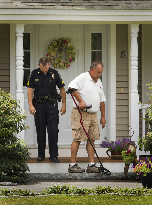 Gorham police Sgt. Michael Nault, left, and Officer Wayne Drown hunt for evidence Saturday at the scene of a shooting at 8 Mountview Drive.