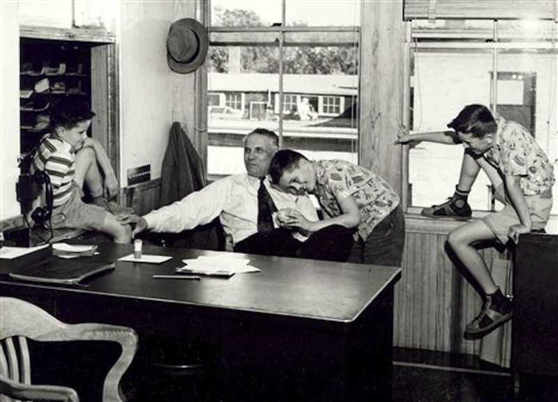 In this 1941 file photo provided by the L.L. Bean Archive, Leon Leonwood Bean spends time with grandsons, from left, Leon Gorman, Jim Gorman, and Tom Gorman, at Bean's office in Freeport, Maine. As outdoors outfitter L.L. Bean celebrates its 100th anniversary, it's still not 100 percent clear what the famous founder's initials stood for. It could be Leon Leonwood Bean, as the company claimed for decades, or was it Leon Linwood Bean, as his grandson suggests. (AP Photo/The L.L. Bean Archive, File)