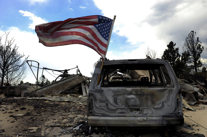 A flag flies on a burned car in Colorado Springs, Colo., where residents were allowed to visit their homes Sunday after the Waldo Canyon fire ravaged their neighborhood.