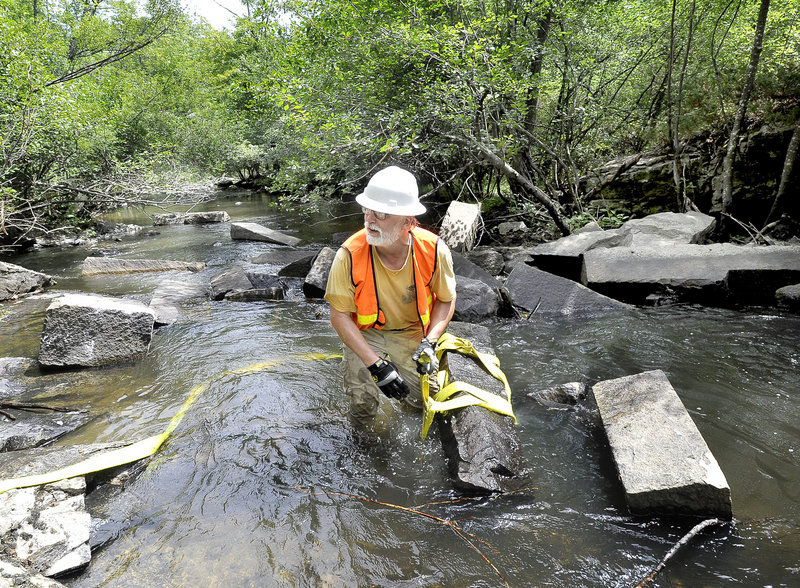 Steven Koenig, executive director of Project Share, secures a strap around a granite block as local, state and federal partnering agencies begin a three-day fish-passage restoration project in the Royal River in Yarmouth on Tuesday.