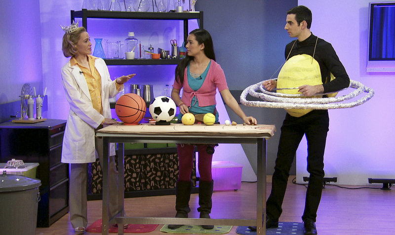 """Erika Ebbel Angle, """"Dr. Erika,"""" left, and her sidekick Don explain the order and relative sizes of the planets in our solar system during taping of the """"Dr. Erika Show"""" in Norwell, Mass. Two episodes are currently available for free online and in New England via Comcast On Demand."""