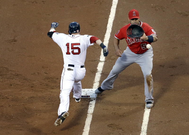 Dustin Pedroia of the Boston Red Sox is safe at first on a dropped third strike as first baseman Albert Pujols of the Los Angeles Angels gathers in the throw. The Angels won, 7-3.