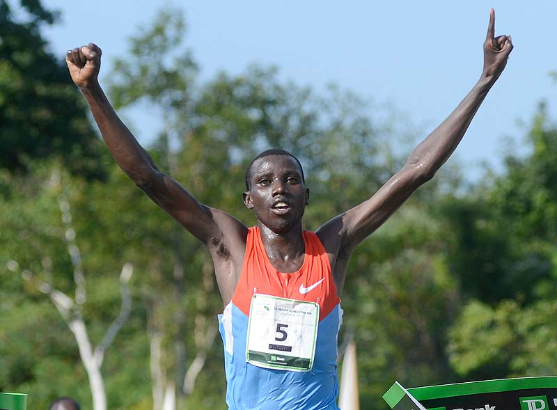 Stanley Biwott of Kenya crosses the finish line first in the 2012 TD Beach to Beacon 10k in Cape Elizabeth Saturday.