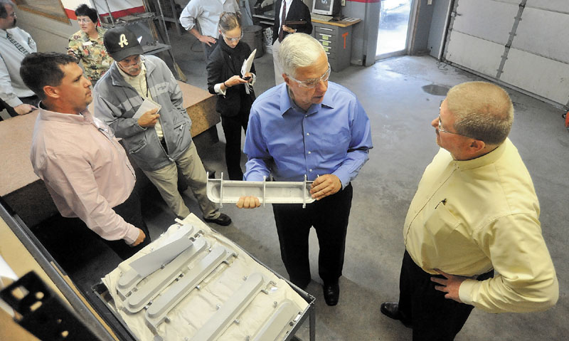 U.S. Rep. Mike Michaud, center, holds a B&B Precise Products fabricated control panel designed for the Boeing 787 Dreamliner with B&B Precise Products owner Will Rood, right and general manager Kevin Wood, far left, during a tour of B&B Precise Products on Neck Road in Clinton on Wednesday.