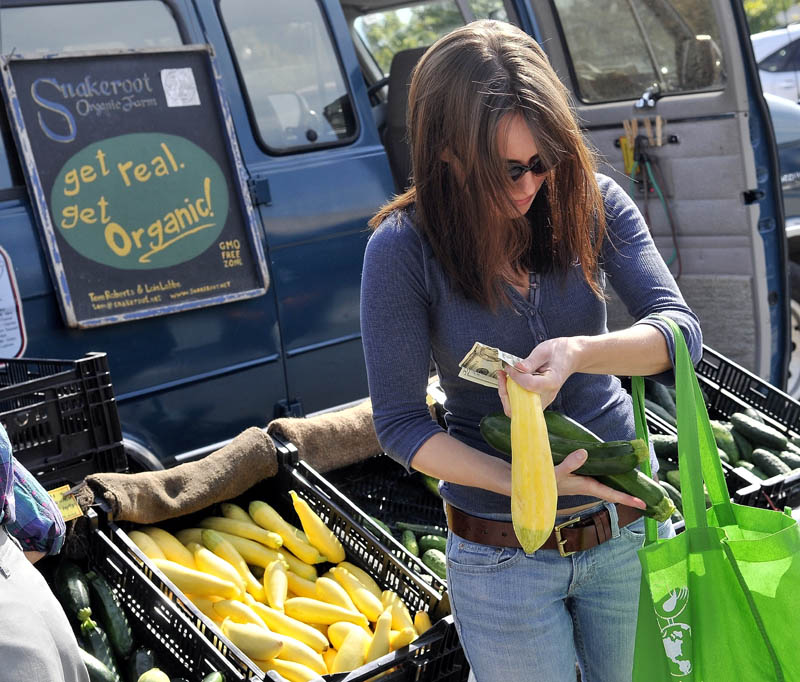 "Kassandra Weese of Albion selects some cucumbers and squash from the Snakeroot Organic Farm stand at the Waterville farmers market at The Concourse on Thursday afternoon. ""I buy organic food for two reasons: to avoid pesticides and buy locally,"" she said."