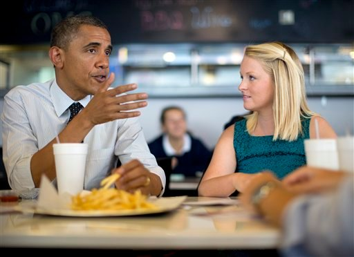 President Barack Obama visits with Emily Young, first-time voter and student and University of Miami, at OMG Burger on Thursday, Sept. 20, 2012, in Miami, Fla. (AP Photo/Carolyn Kaster)