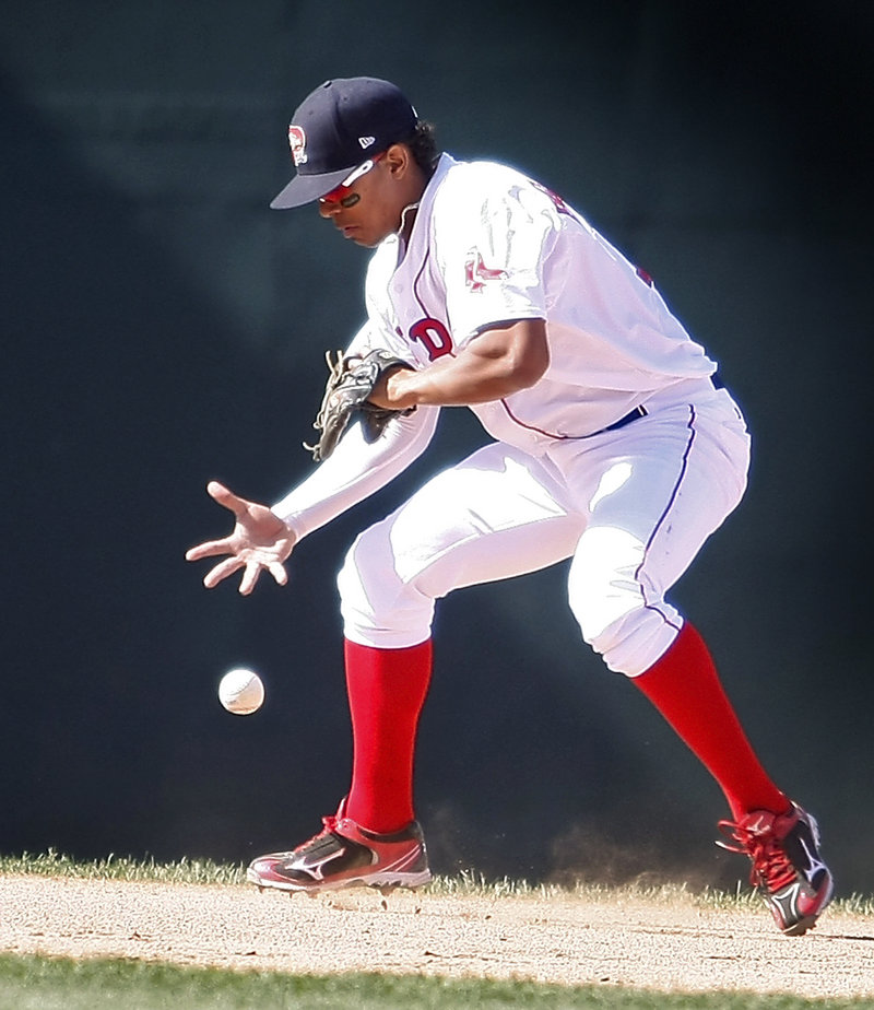 Sea Dogs shortstop Xander Bogaerts struggles to contain a grounder in Monday's game at Hadlock Field. Bogaerts was charged with an error.