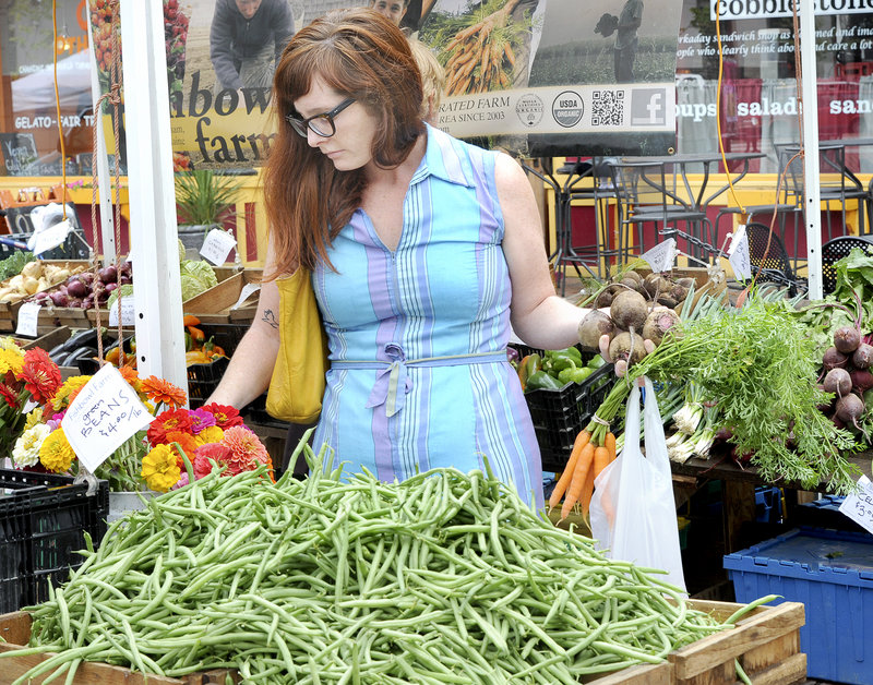 """Beth Taylor of Portland shops at the Fishbowl Farm stand Wednesday at the Portland farmers market in Monument Square. She said she tries to buy organic because she wants """"clean food"""" grown mostly free of such things as pesticides and synthetic fertilizers."""