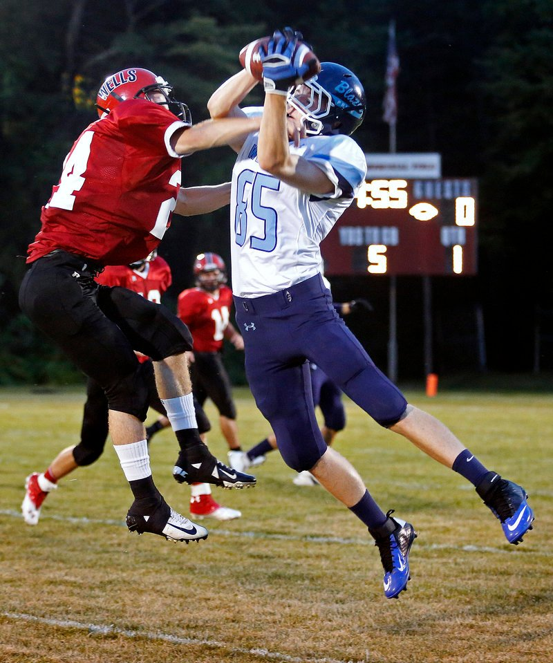Aaron Duncanson of Westbrook hauls in a first-quarter pass Friday night as Joey Spinelli defends for Wells. Westbrook earned a 28-20 victory on the road.