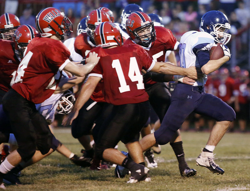 Collin Joyce of Westbrook breaks through the Wells defense in the first quarter Friday night in their early-season Western Class B showdown. Joyce rushed for 48 yards and also caught two touchdown passes in a 28-20 victory for the Blue Blazes