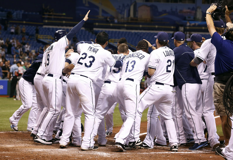 B.J. Upton of the Rays gets mobbed by teammates after hitting a winning three-run homer to cap a six-run ninth inning Thursday night at St. Petersburg, Fla. Boston had a 4-1 lead entering the bottom of the ninth.