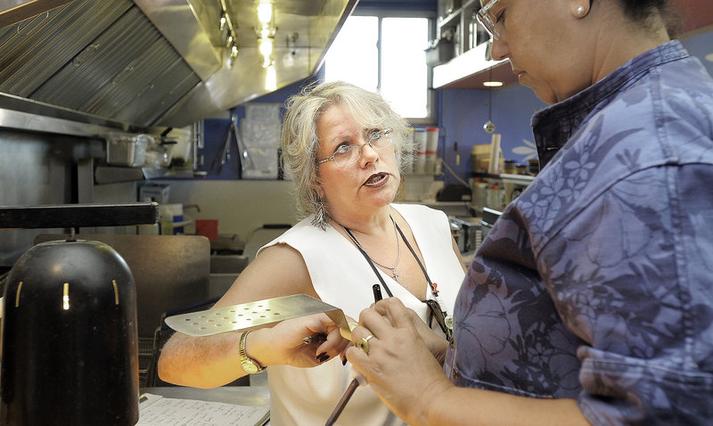 Portland health inspector Michele Sturgeon, left, talks with executive chef Cheryl Lewis in El Rayo Taqueria's kitchen during inspection Monday. The city admits it lacks the resources to inspect restaurants on a regular basis.