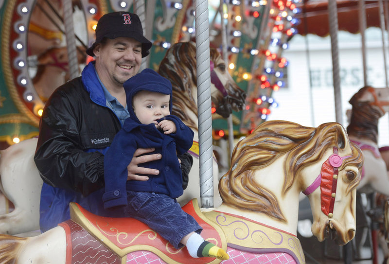 Kempton Rich of Sebago holds his 13-month-old son, Kayden, on the merry-go-round at the Fryeburg Fair on Sunday. It was Kayden's first ride on a merry-go-round.